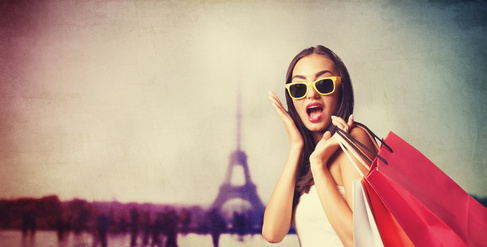 Brunette girl with shopping bags on Parisian background.